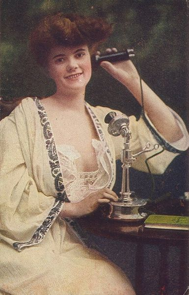 Woman using telephone, c. 1910.