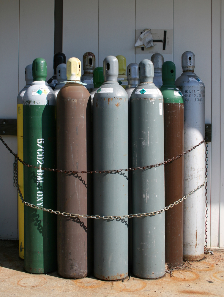 An assortment of compressed gas tanks chained to a wall at Duke University in Durham, North Carolina