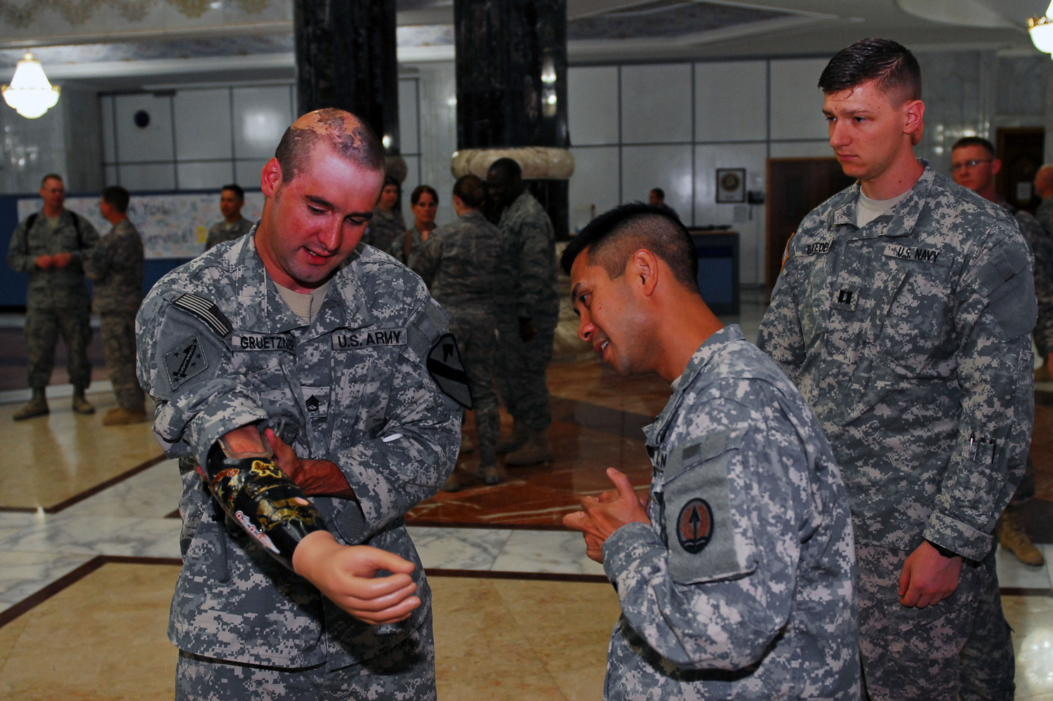 Retired Staff Sgt. Bradley K. Gruetzner explains his prosthetic arm to servicemembers at Al Faw Palace, Camp Victory, Iraq, June 21.