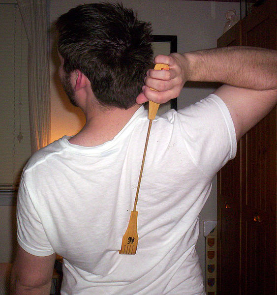 Man scratching back with a Backscratcher
