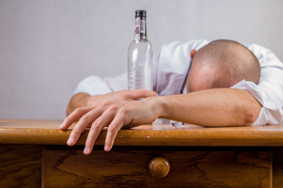 A hungover man collapsed face down on a table cradling a bottle.