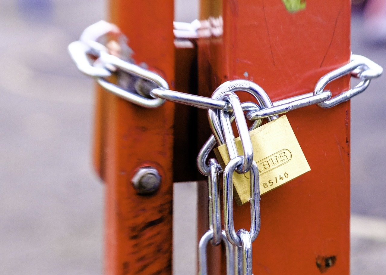 A locked chain holding together an orange metal door