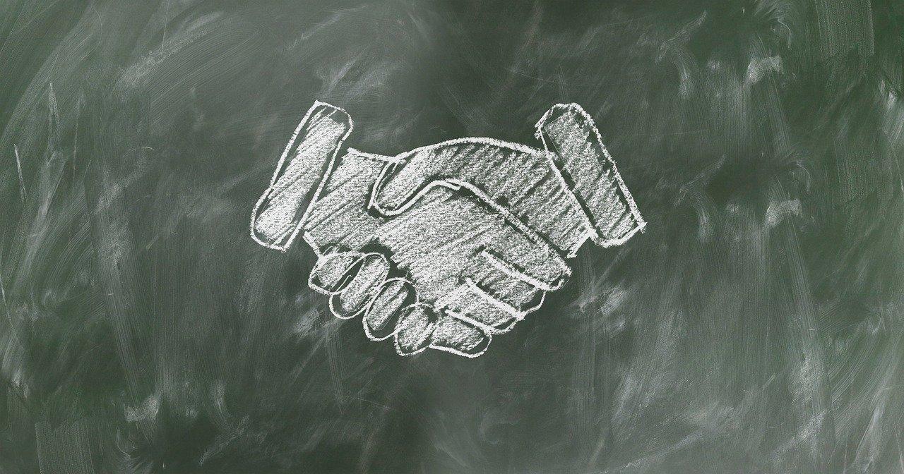 A handshake drawn on a chalkboard.