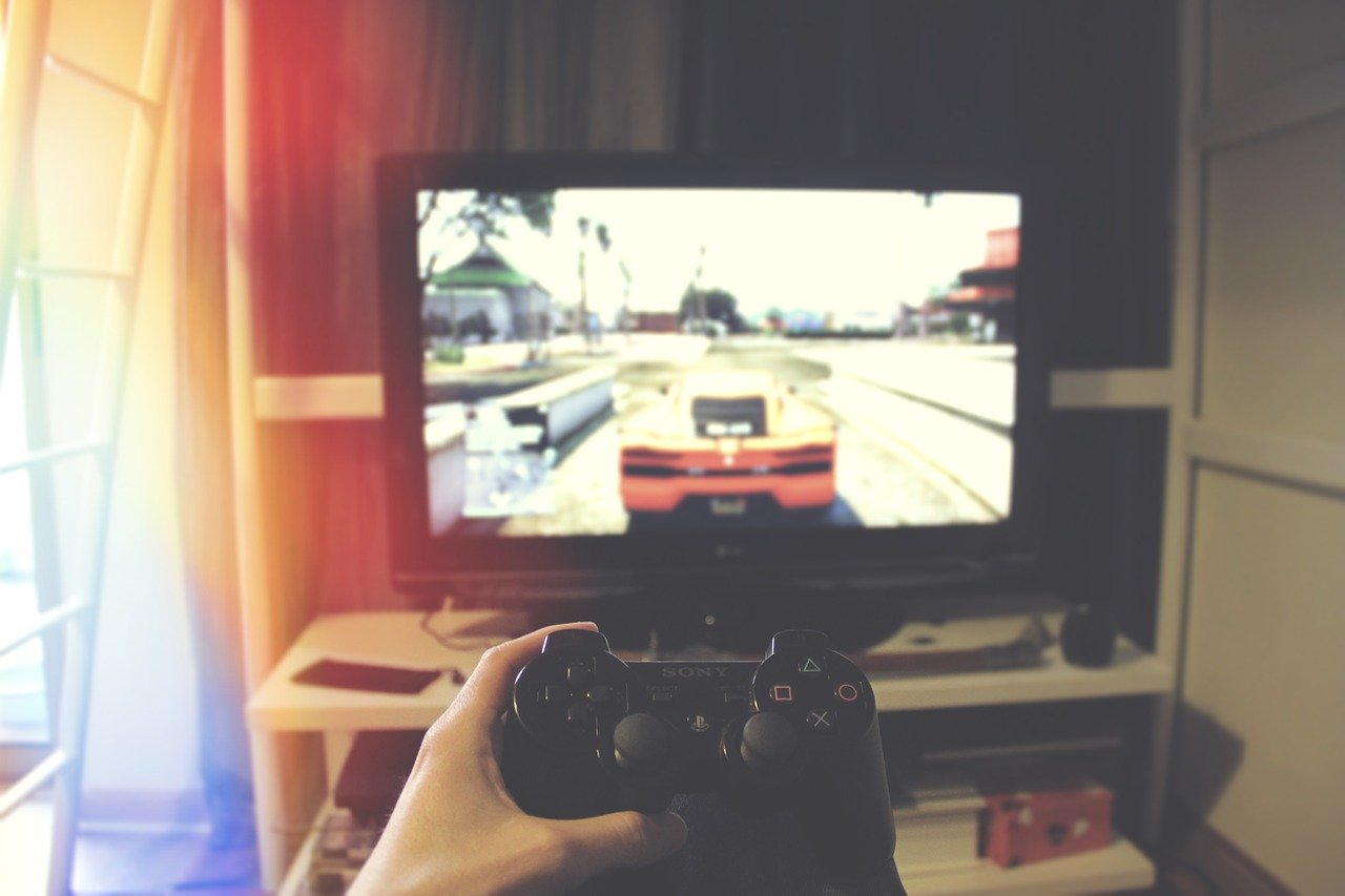 A person holding a controller in front of a TV, playing a car racing game