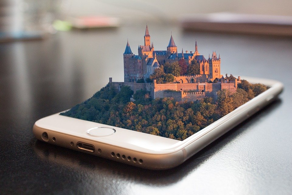 A smartphone with a castle and forest coming out of the screen in 3D.