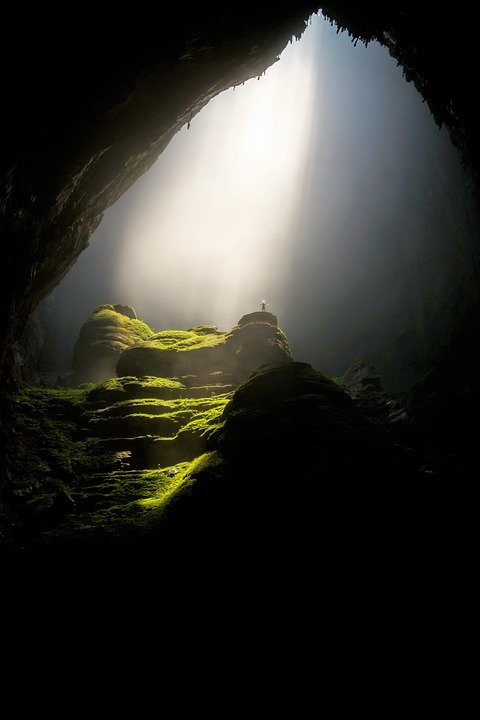 A cave arch with light coming through the ceiling on the other side