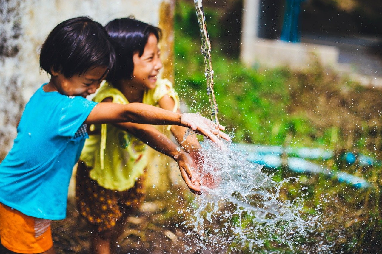 a photo of children smiling by a water fountain