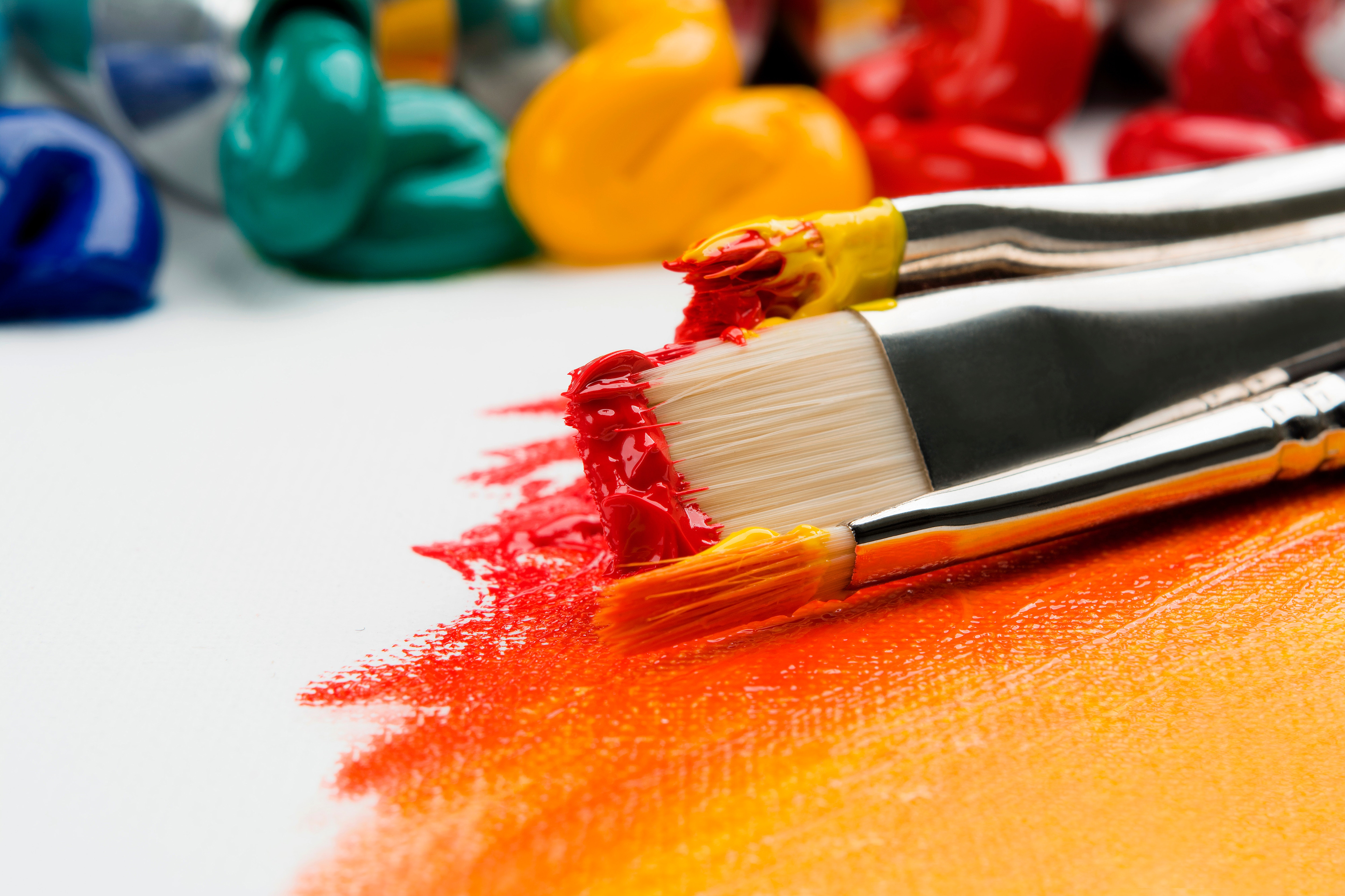 Paintbrushes dipped in yellow and red
