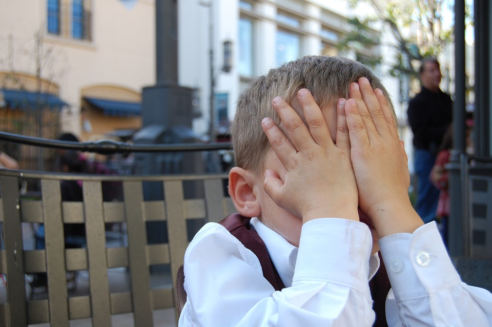 Small boy covering his face with hands