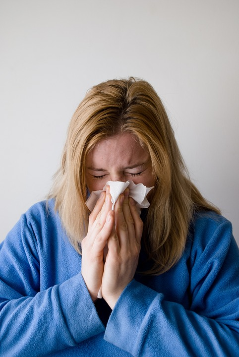A woman sneezing into a tissue.