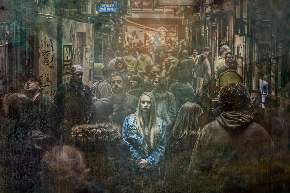 A woman stands in a washed-out, ghostly crowd.