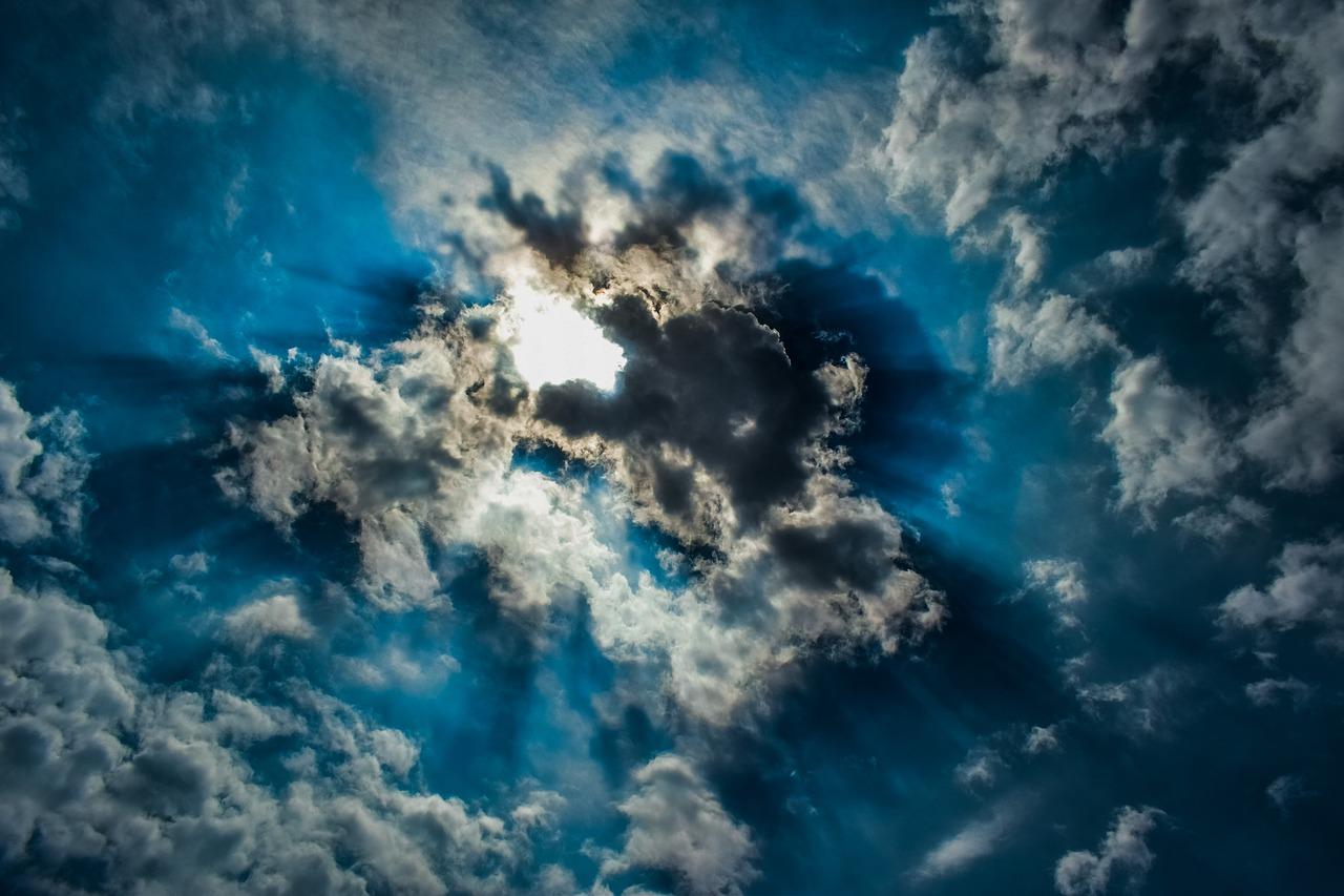 The sun shining through clouds.
