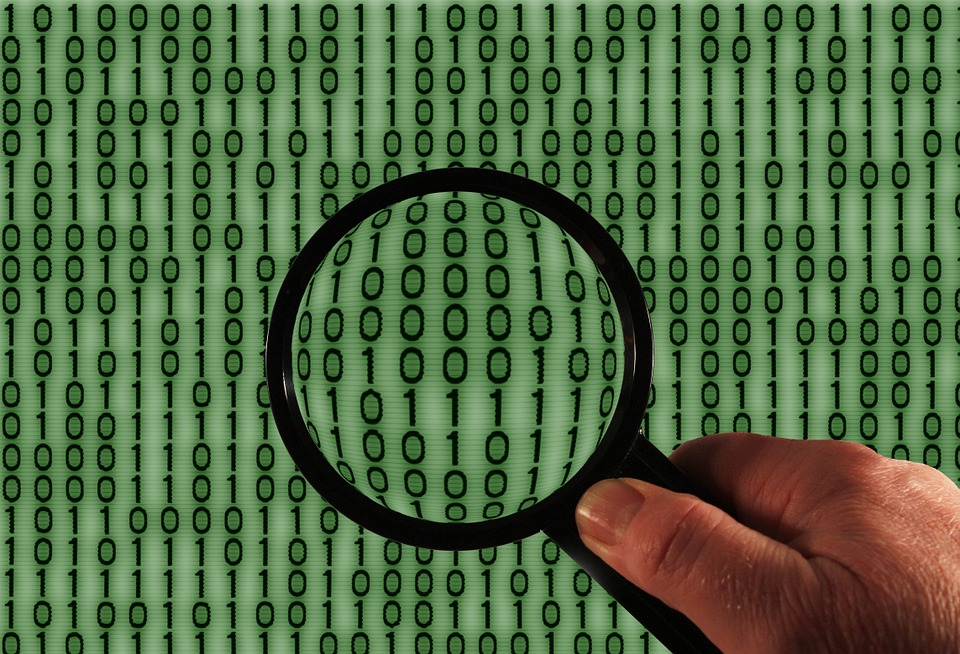 A magnifying glass in front of binary code.