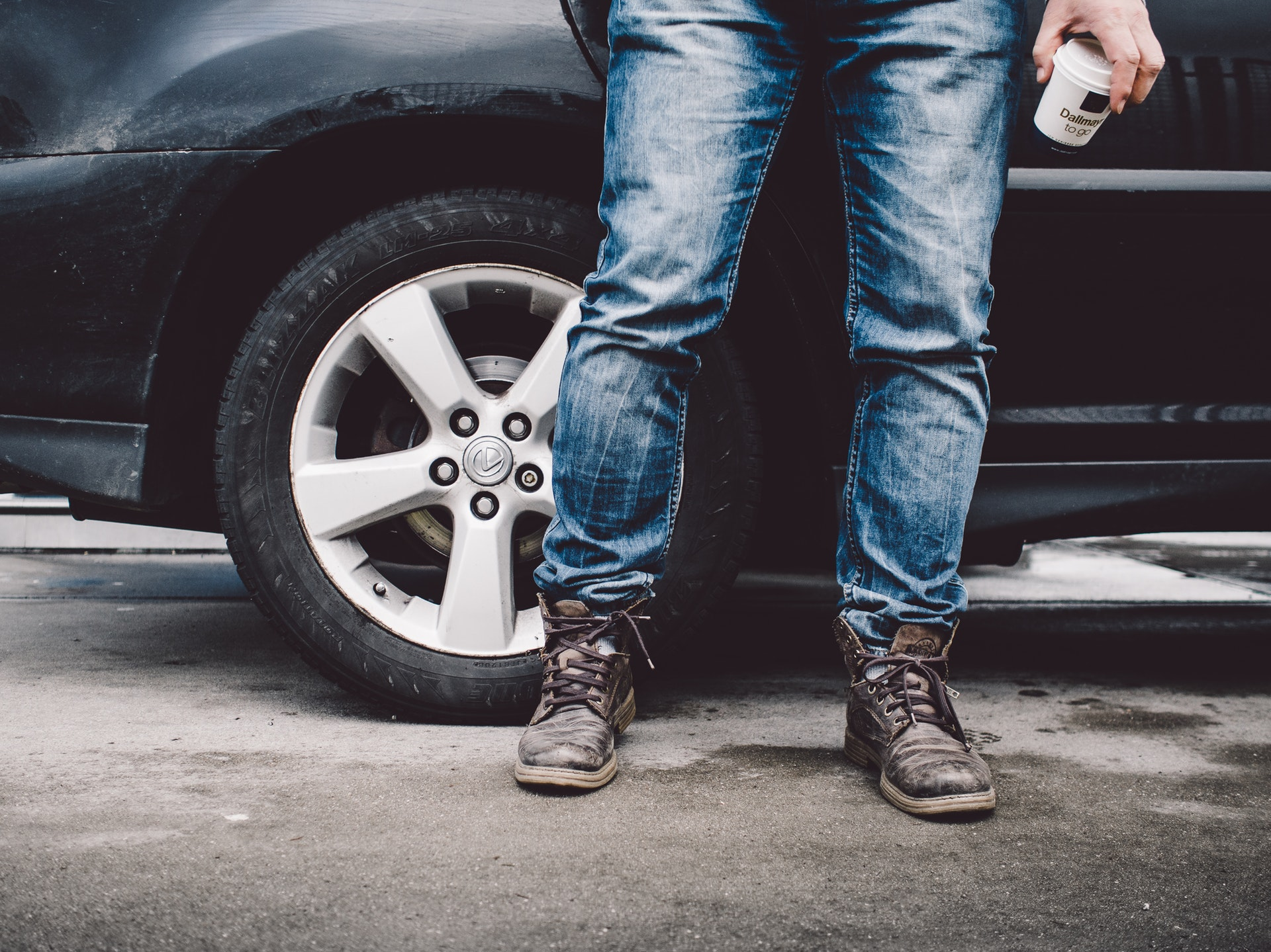 Person wearing jeans standing next to a car