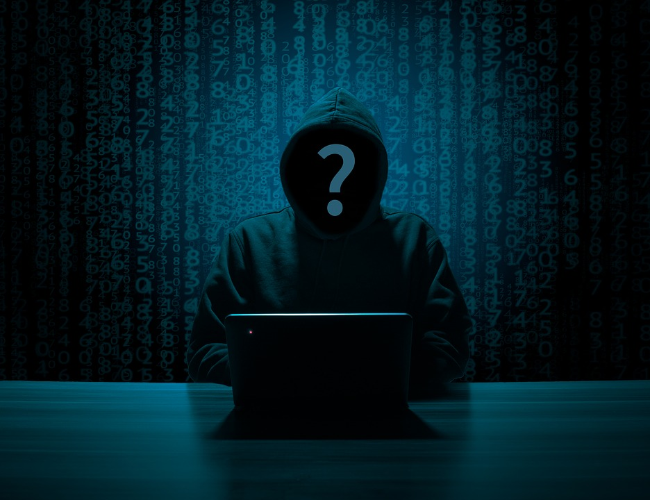 The image shows a hooded person hacking a laptop.