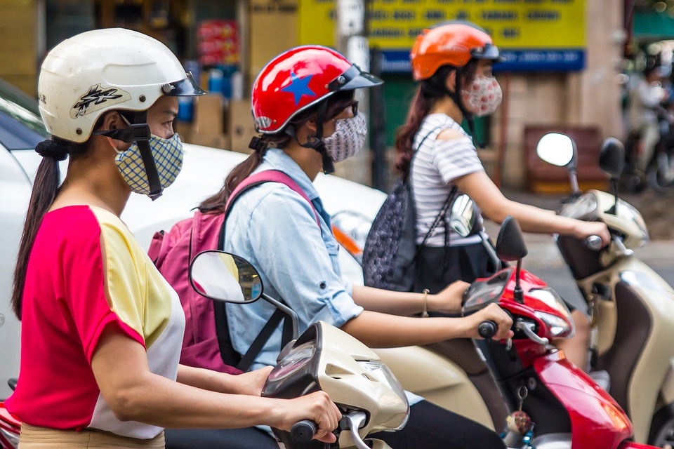 Girls riding motor scooters, wearning facemasks against air pollution