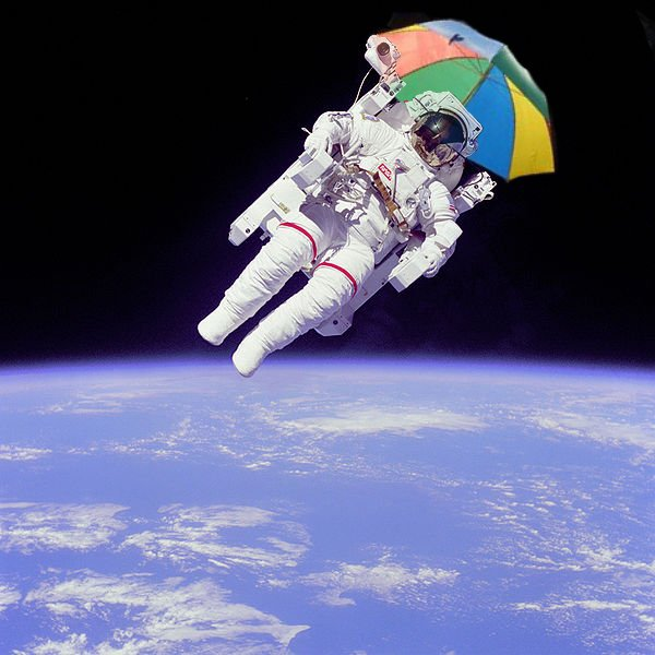 Astronaut Bruce McCandless II, mission specialist, participates in a extra-vehicular activity (EVA), a few meters away from the cabin of the shuttle Challenger. With an umbrella.