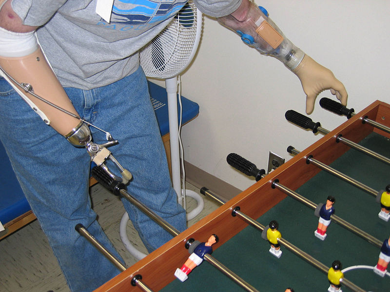 A soldier in the U.S. Army plays fooz-ball with two prosthetic limbs.