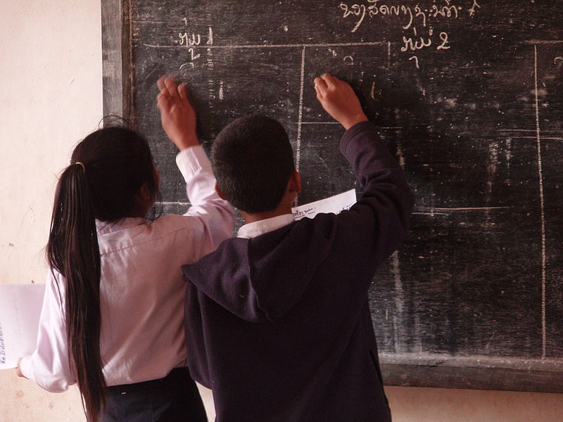 Schoolchildren writing on a blackboard