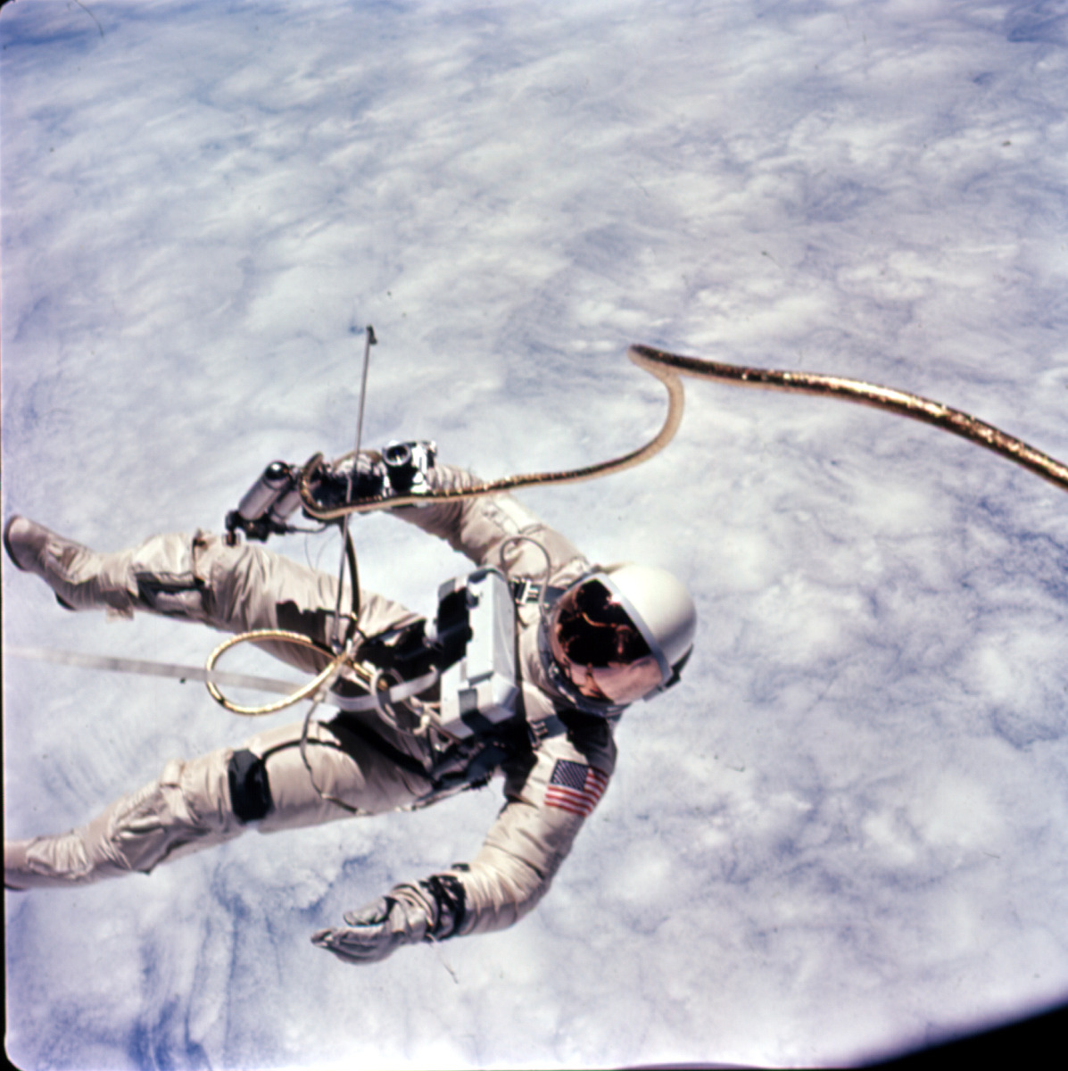 This photograph was taken early in the EVA over a cloud-covered Pacific Ocean. Astronaut Edward H. White II, pilot for the Gemini-Titan 4 space flight, floats in zero gravity of space. The extravehicular activity was performed during the third...