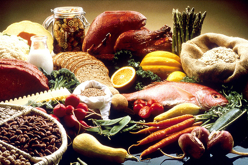 This image shows a display of healthy foods on a table. Foods include beans, grains, cauliflour, cantelope, pasta, bread, orange, turkey, salmon, carrots, turnips, zucchini, snowpeas, string beans, radishes, asparagus, summer squash, lean beef,...