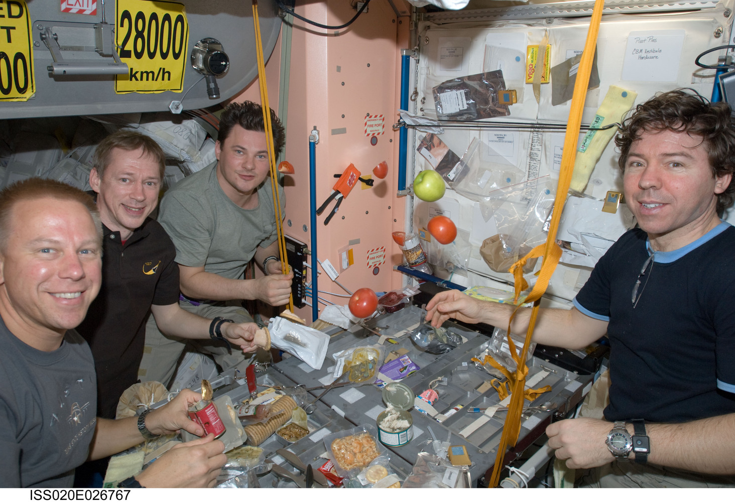 NASA astronaut Tim Kopra (left), European Space Agency astronaut Frank De Winne, cosmonaut Roman Romanenko and NASA astronaut Michael Barratt, all Expedition 20 flight engineers, share a meal at a galley in the Unity node of the International Space...