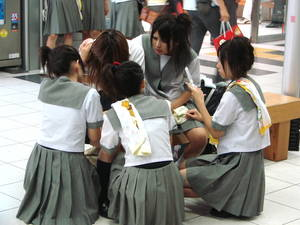A group of Japanese school girls using mobile phones