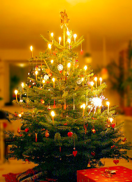 A Danish Christmas tree illuminated with burning candles, adorned with homemade Christmas decorations such as red hearts, white paper snowflakes, a golden star at the top, and gifts stacked underneath.