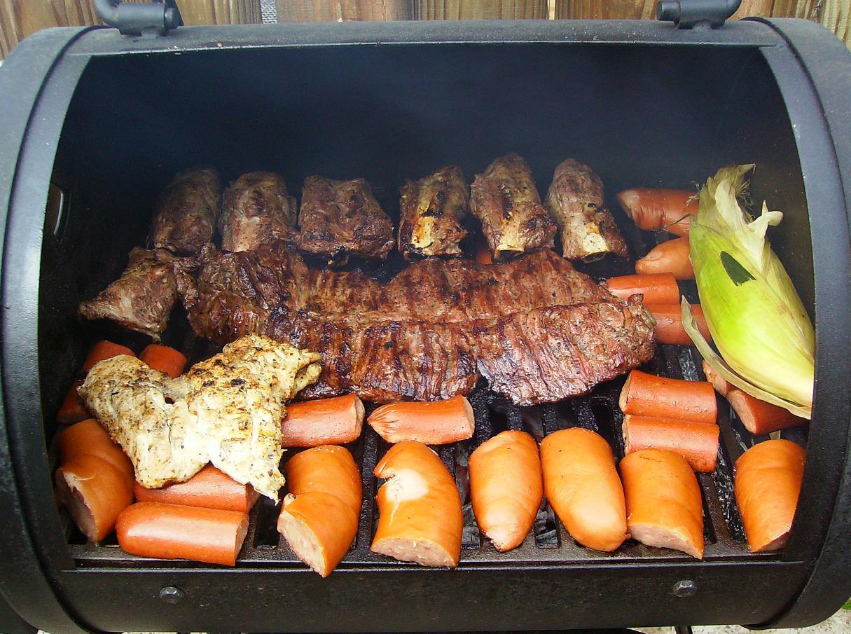 A typical Laredo, Texas BBQ grill - Fajita center, Chicken left, Ribs above, Sausage bottom, Corn right.