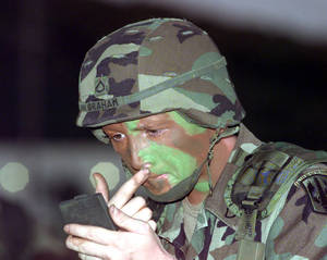 PFC Joel Graham puts on camouflage paint