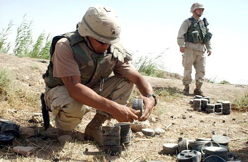 A U.S. Army engineer removing the fuse from a Russian-made mine in order to clear a minefield outside of Fallujah, Iraq
