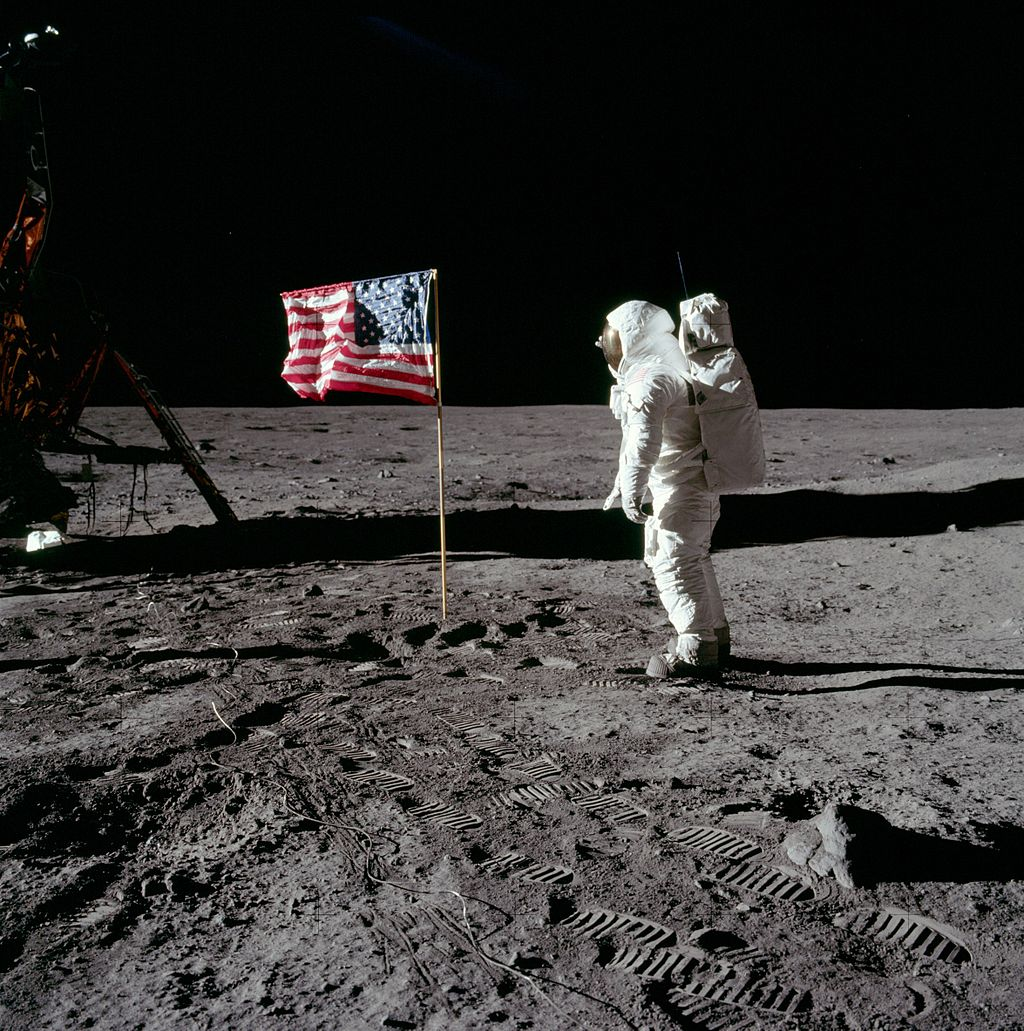 Astronaut Buzz Aldrin poses for a photograph beside the United States flag