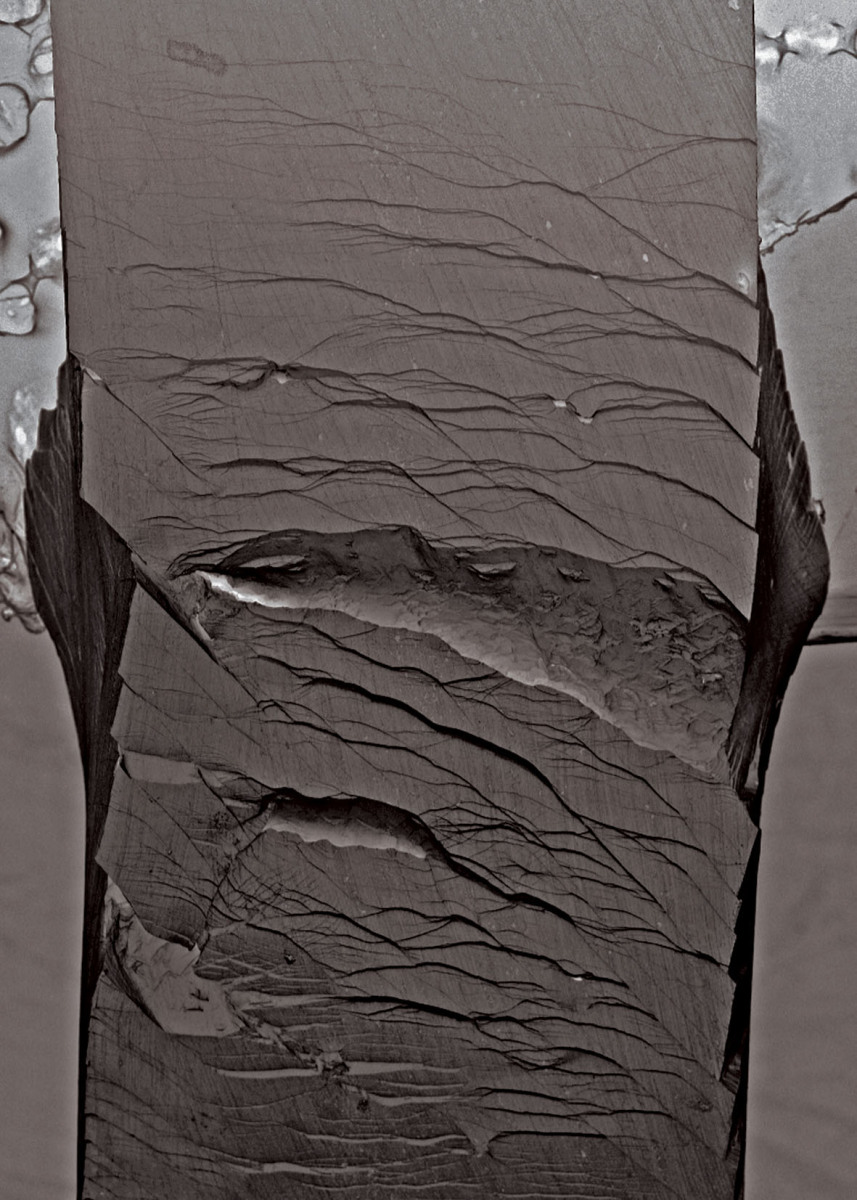 Secondary electron micrographs taken after a bending test on an unnotched Pd79Ag3.5P6Si9.5Ge2 glassy specimen.