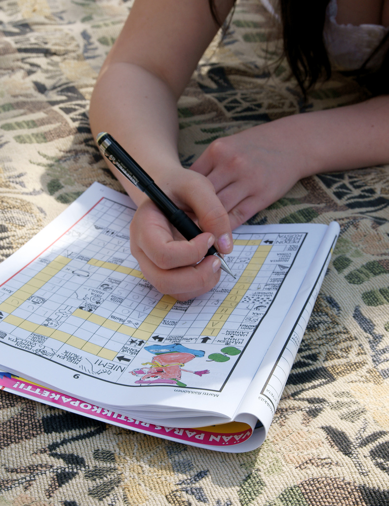 Person solving Finnish crossword puzzle
