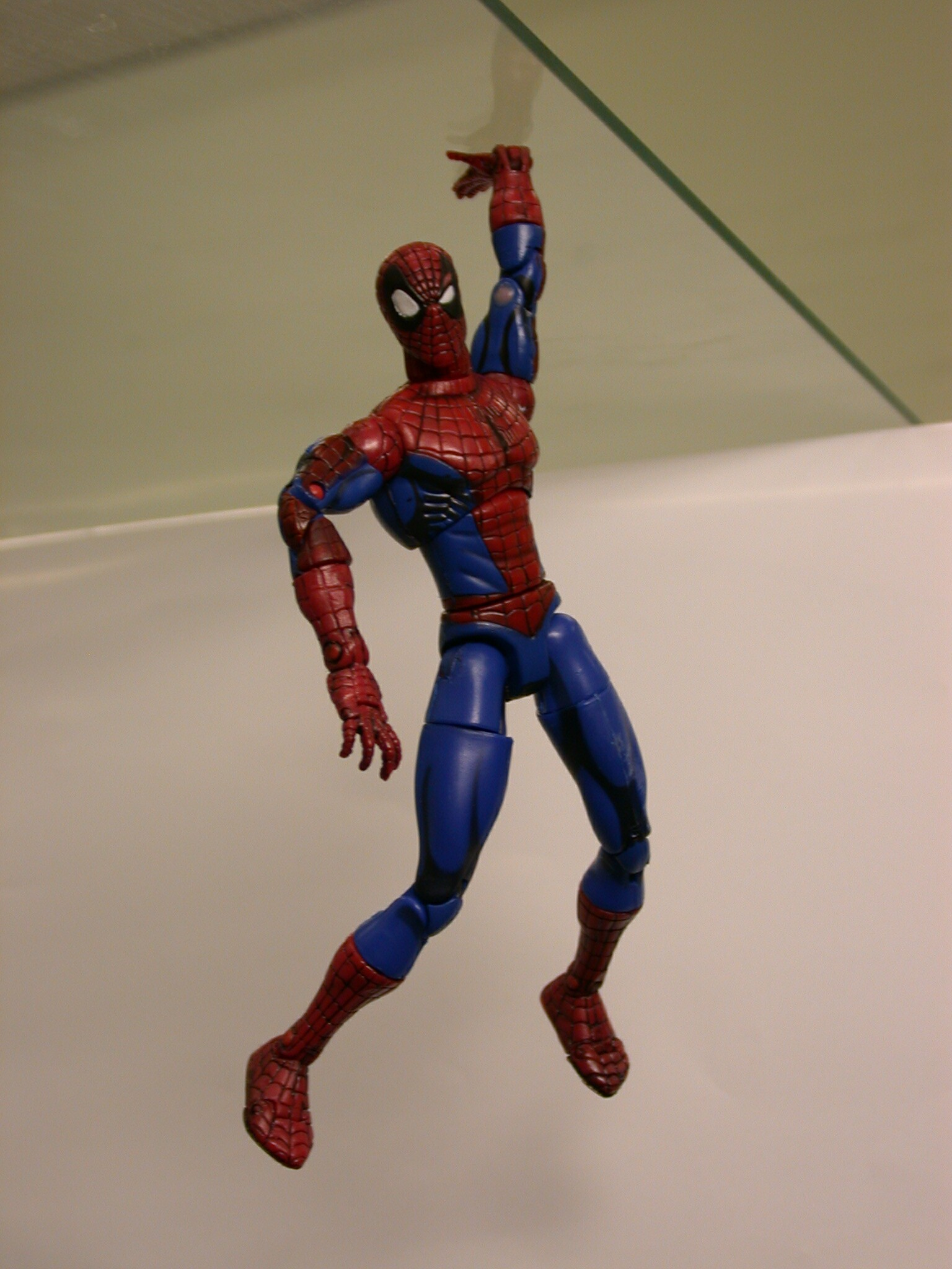 Spiderman toy hanging from a glass plate, attached using the tape with a contact area of approximately 0.5cm2 with a carry load of >100g. This toy has been attached to several surfaces before this photo was taken.