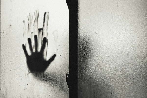 Bloody handprint on window pane
