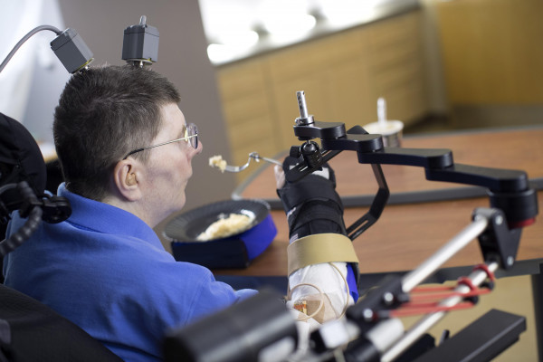 A brain-computer-interface helps a paralysed man to feed himself for the first time in 8 years.