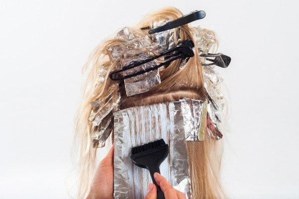 Applying hair dye to woman's hair