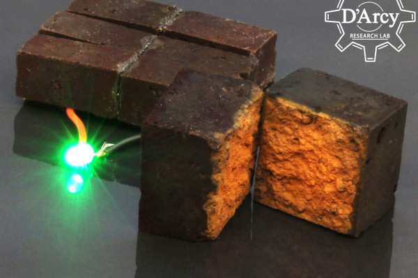 A brick, modified to store power hooked up to a glowing LED. A second brick is cut in half to show the interior