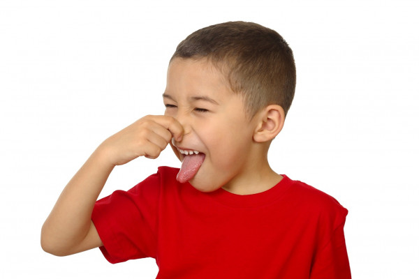 Kid smelling something bad and holding his nose