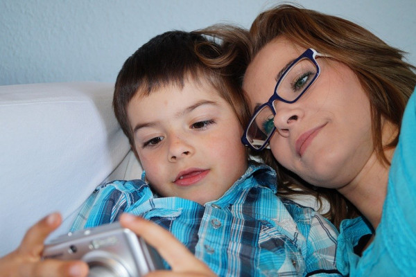 A mother and her son looking at photos on a camera.