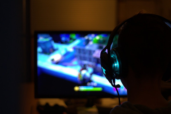 View of a person's head from behind with headphones on playing a video game.