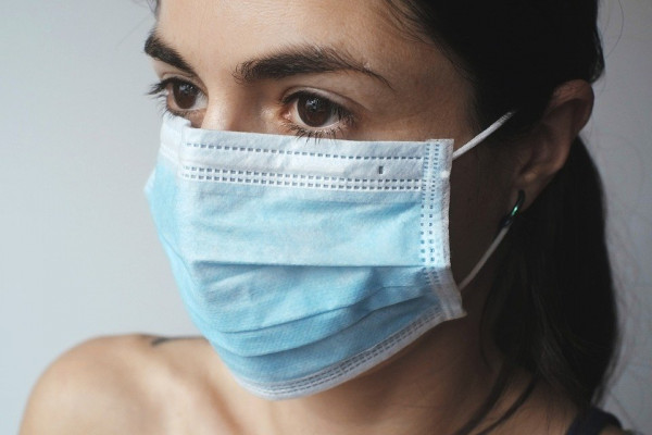 A woman wearing a blue facemask.