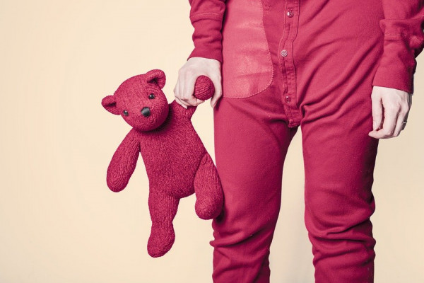 person in pink pyjamas holding pink teddybear