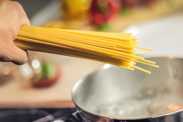Spaghetti being added to a pot