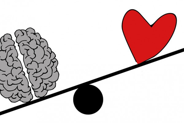 A cartoon brain outweighing a cartoon heart on a balance scale.