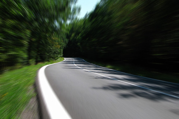 A photo taken from on the road while the trees blur due to speed