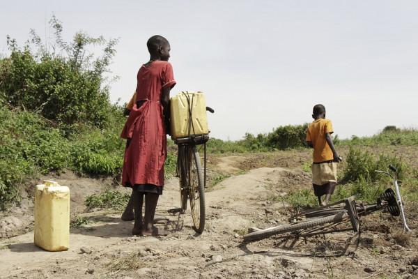 Three children walking bikes on a dirt road in Uganda.