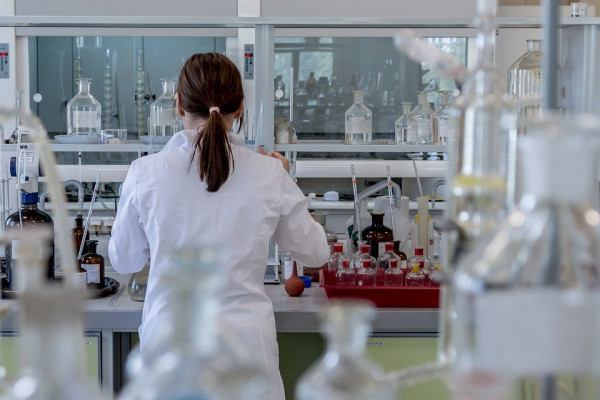 A woman with her back to the camera in a lab, using scientific equipment