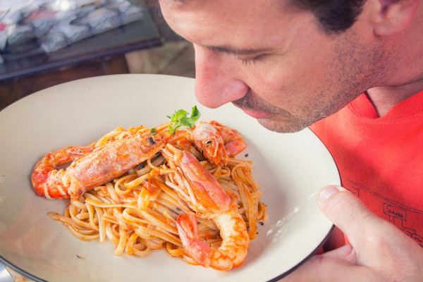 photo of a man smelling some pasta